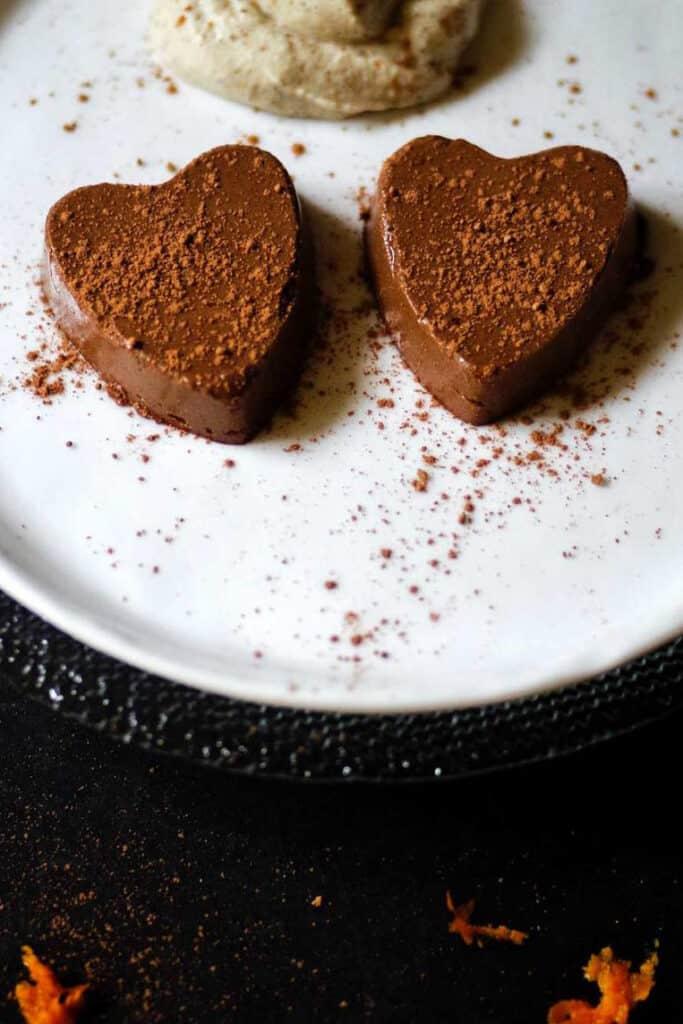 Two chocolate semifreddo truffles on a white plate