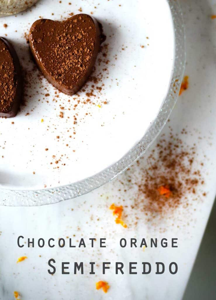Two chocolate orange semifreddo truffles on a white plate with cacao and orange zest sprinkles