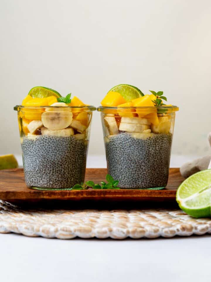 Two chia puddings on a wood tray topped with tropical ingredients
