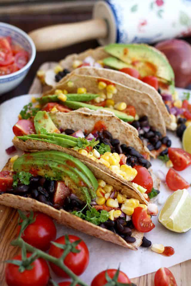 beans, veggies, avocado lined up in folded tortillas