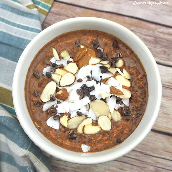 a white bowl on wood filled with chocolate chia pudding topped with coconut, chocolate, almonds