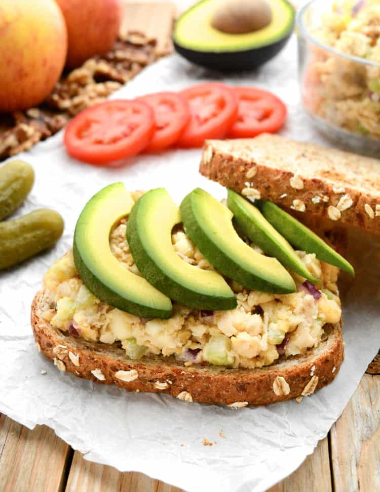 apple walnut chickpea salad on sliced bread topped with avocado