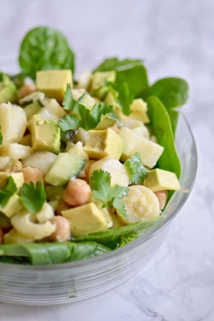 greens with chickpeas and avocado in a bowl
