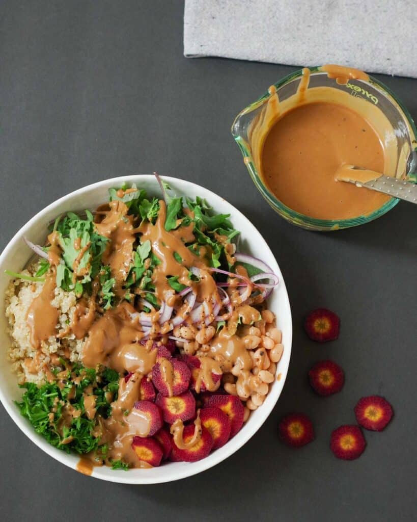 grains, greens, veggies, and pulses topped with balsamic tahini sauce in a bowl