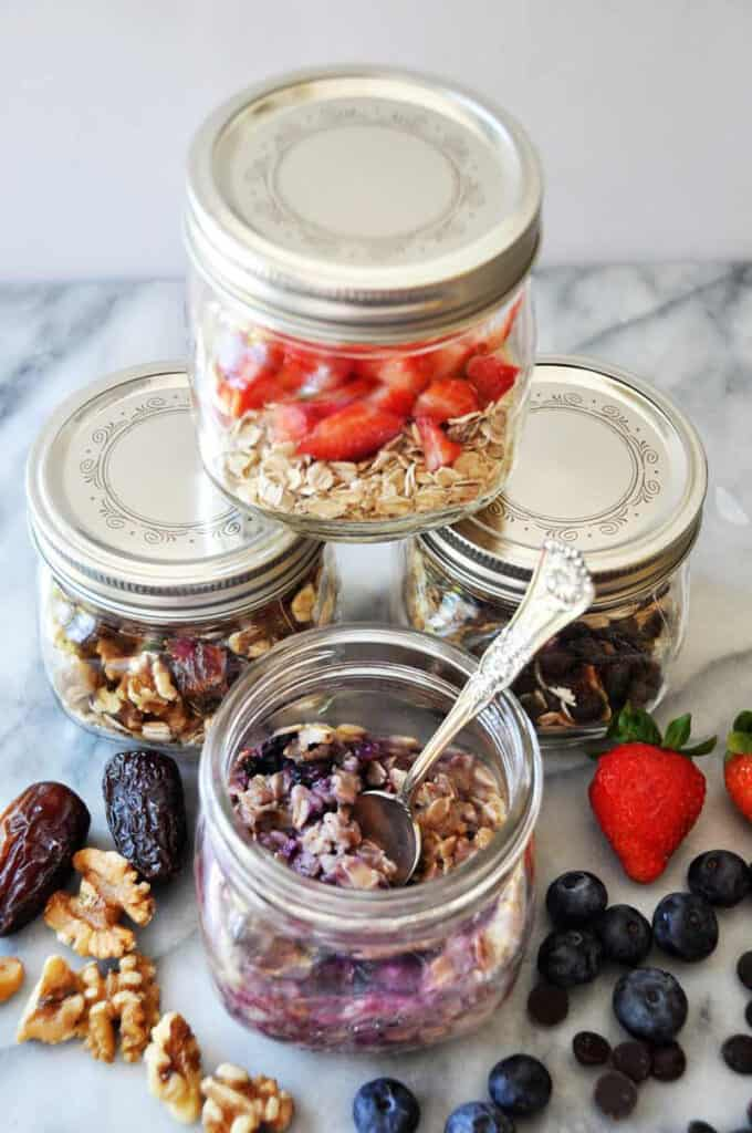 four small jars of various oatmeal and fruit mixes on a marble table