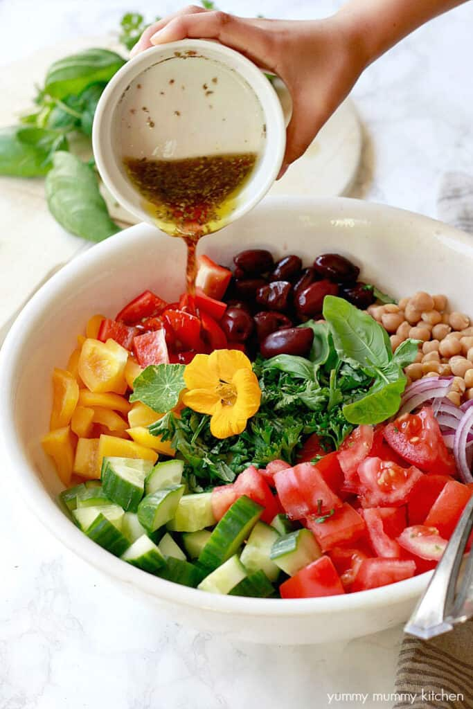 a rainbow of vegetables in a bowl with salad dressing pouring over