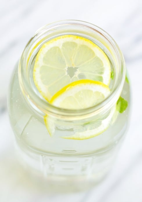 lemon slices an mint sprigs in a mason jar filled with water