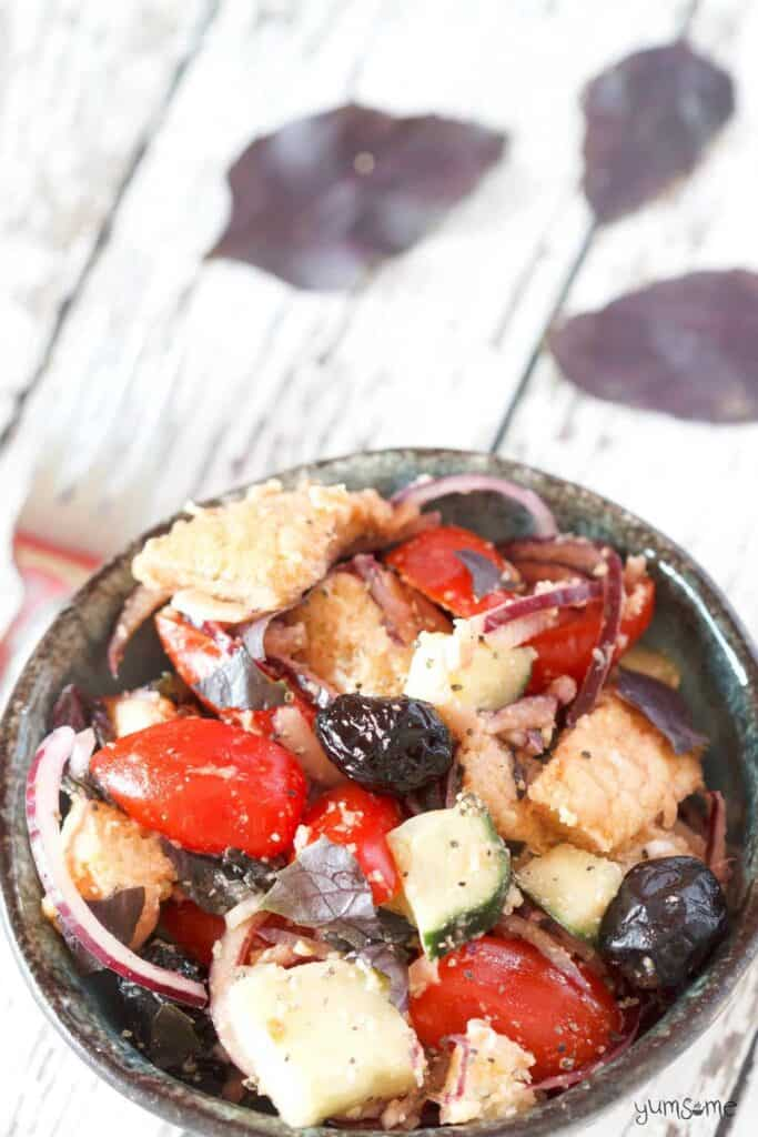 bread squares, cherry tomatoes, red onions and olive salad in a bowl