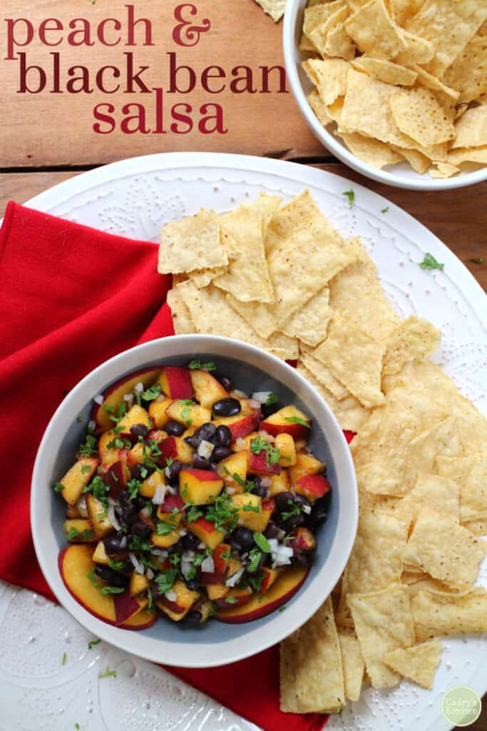 peach and back bean salsa in a bowl surrounded by tortilla chips