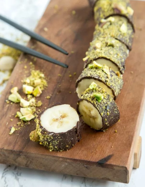 a banana covered in chocolate and pistachios and sliced into bite-sized pieces