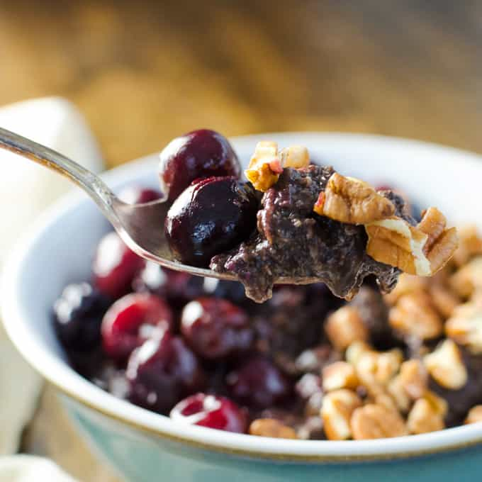 cherries and chocolate with oatmeal in a blue bowl