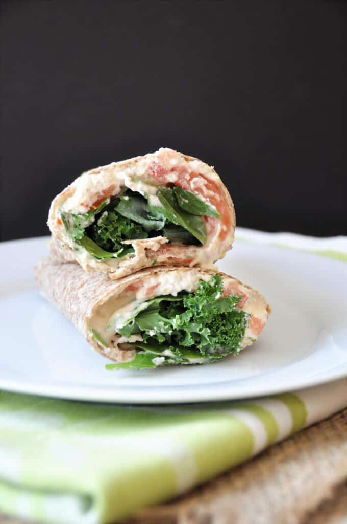 greens and hummus in a wrap stacked on a plate