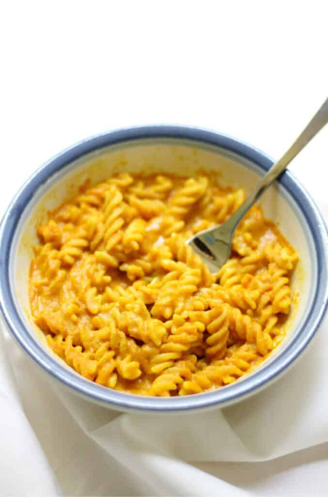spiral noodles coated in cheesy sauce in a blue-rimmed bowl