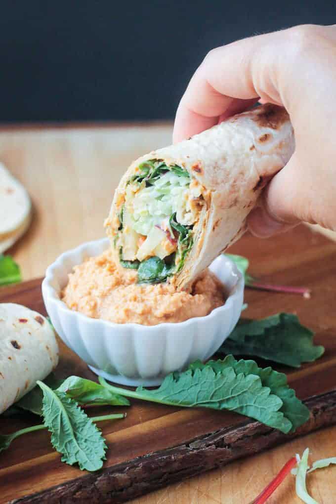 veggie wrap dipping into a dip