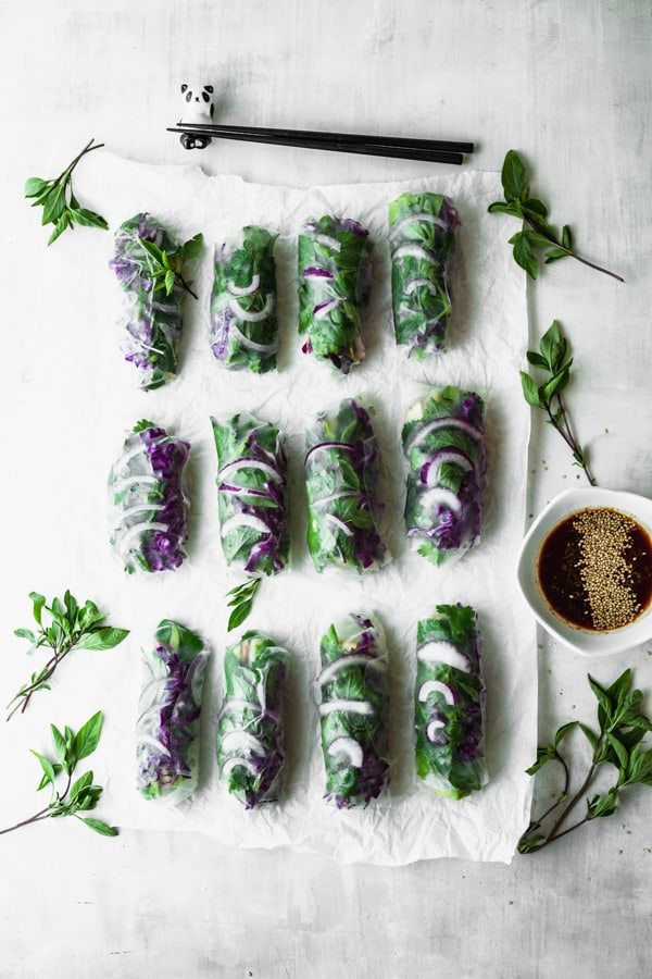 12 green and purple summer rolls on parchment paper