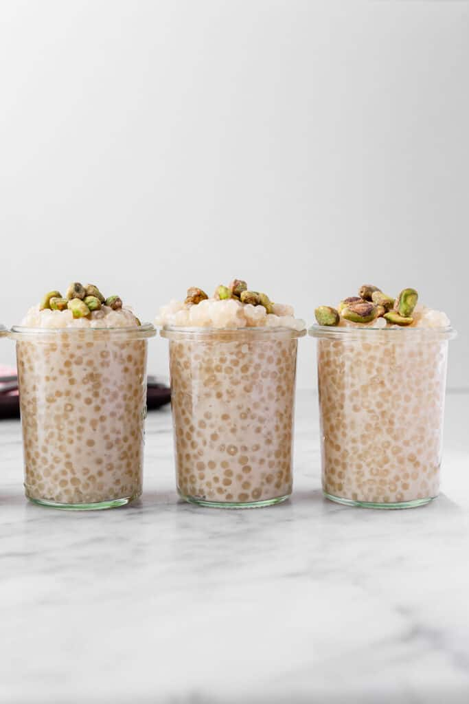 three jars of vegan vanilla tapioca pudding topped with pistachios