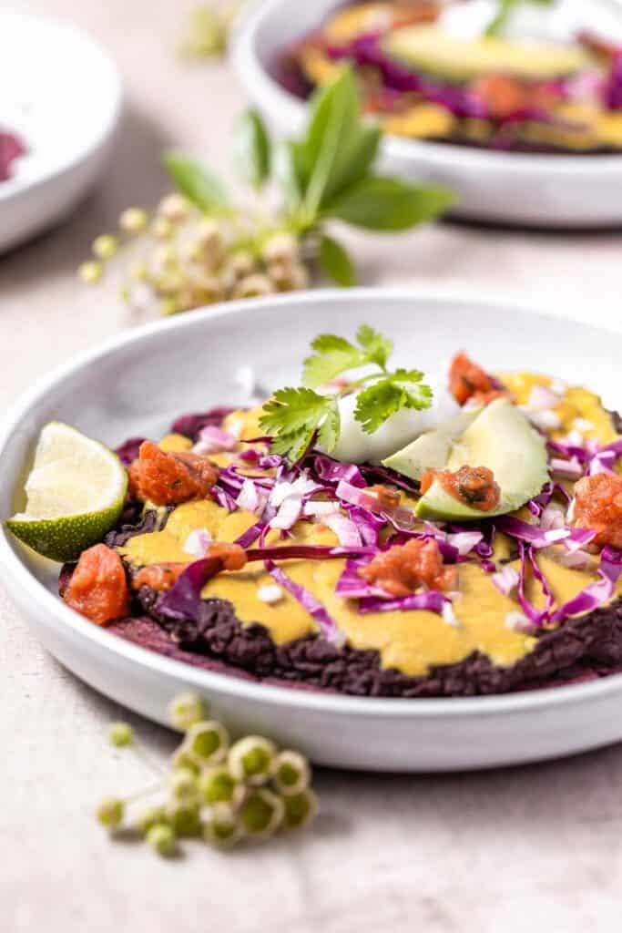 refried beans, vegan cheese, salsa, purple cabbage, lime, avocado, vegan sour cream and cilantro over a purple flatbread