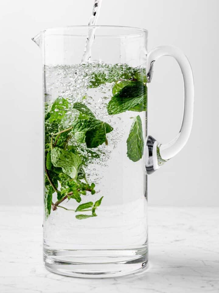 A tall pitcher filling with fresh mint water