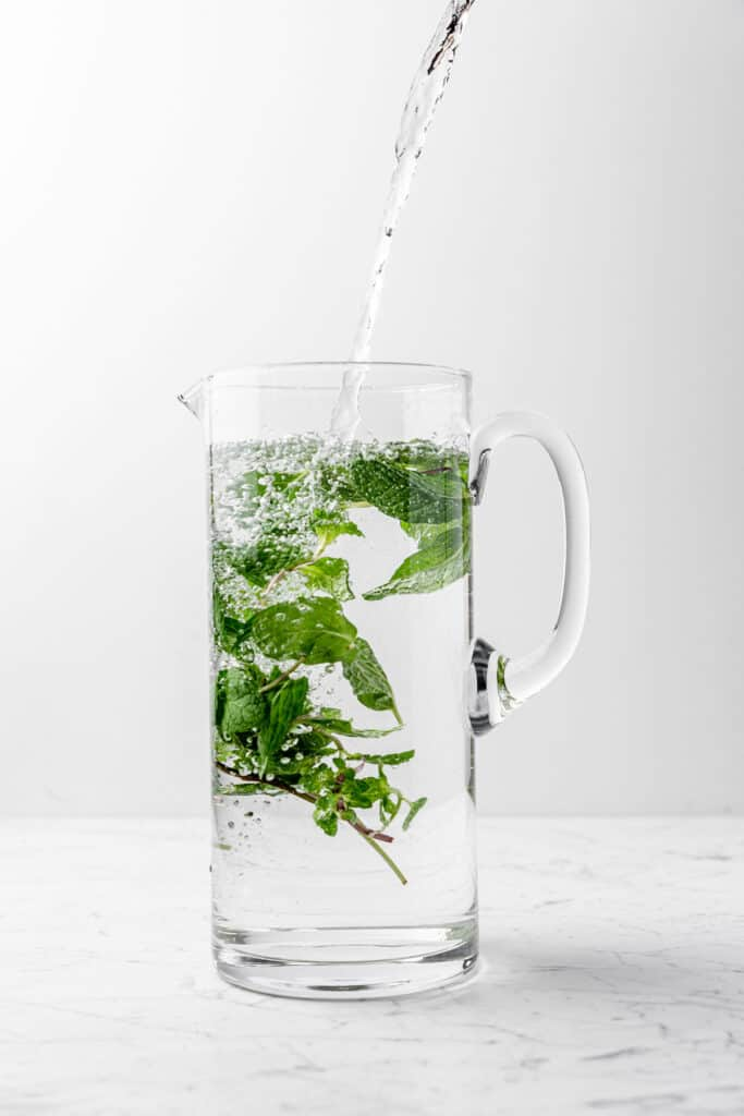 Tall pitcher filling with water and fresh mint leaves
