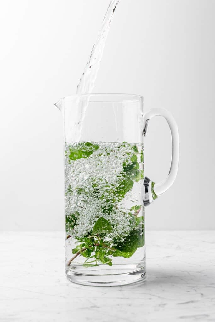 A tall pitcher of mint water with water pouring in from the top, creating bubbles throughout the 70% full pitcher