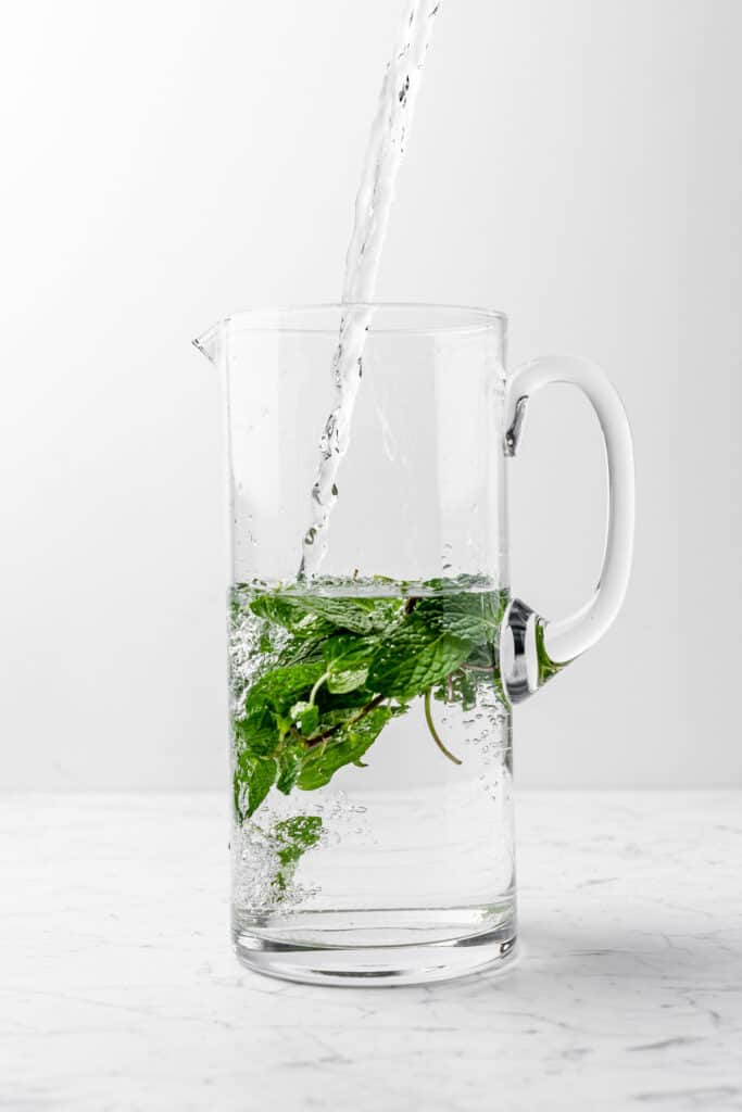 A tall pitcher of fresh mint water being filled while half full