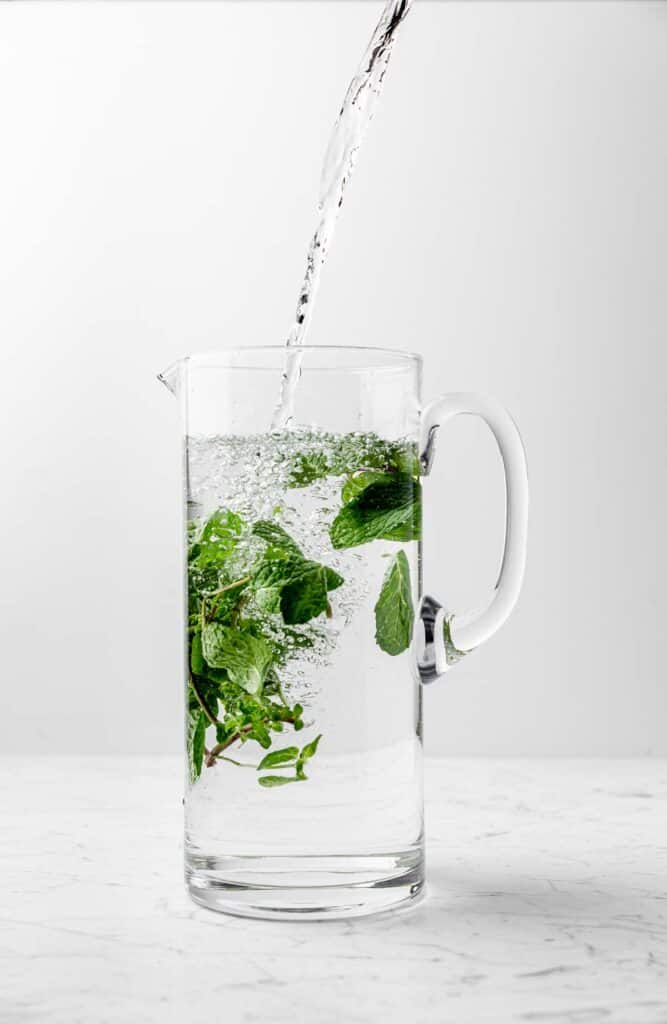 Water filling a pitcher with fresh mint sprigs