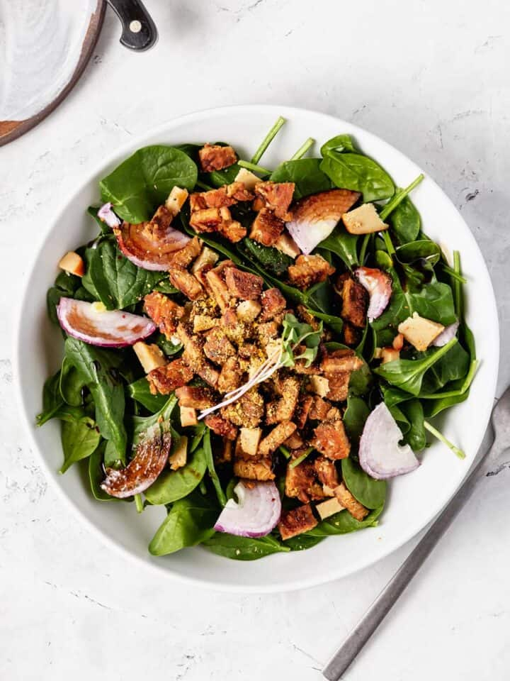 A bowl of spinach salad with tempeh bacon, red onion, and artisan vegan cheese