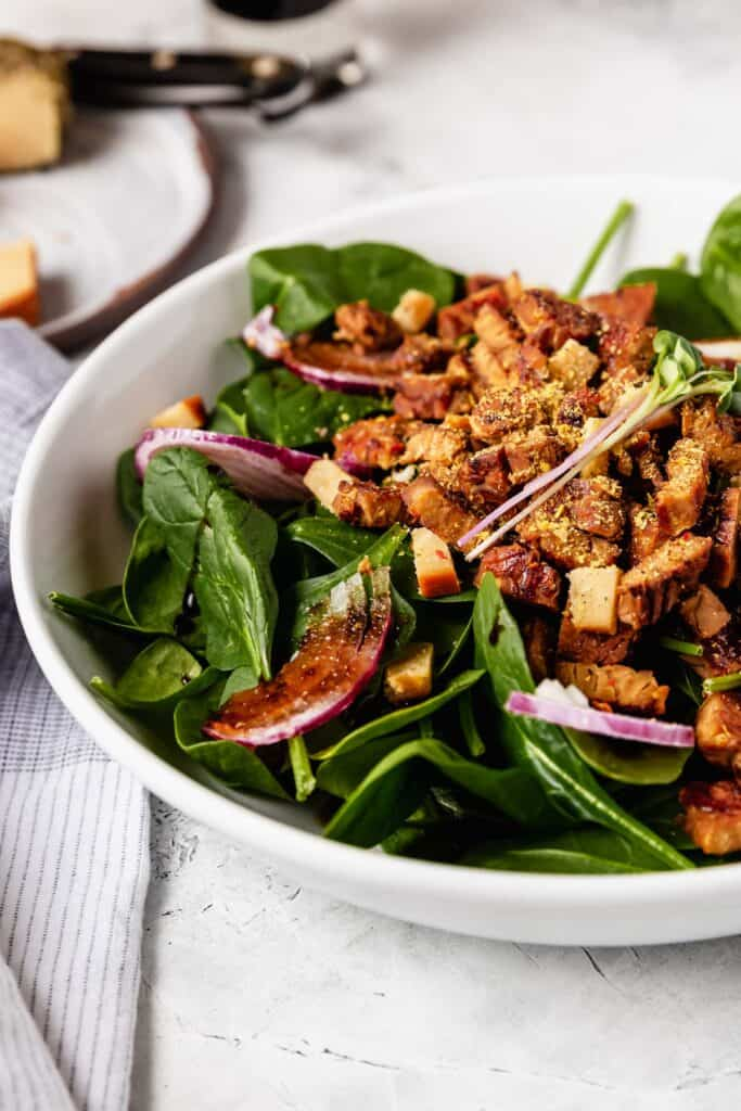 A side view of a big bowl of spinach salad topped with shaved red onion and tempeh bacon