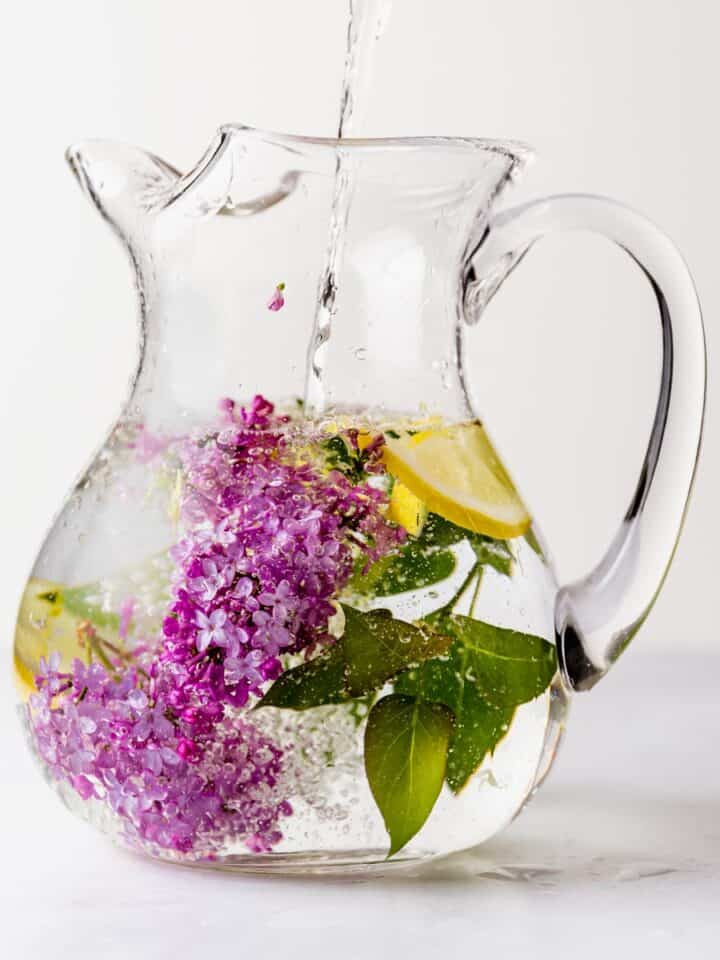 Lilac and lemons flavoring water in a pitcher