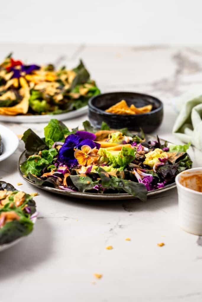 A few plates full of vegan taco salad and a bowl of tortilla chips