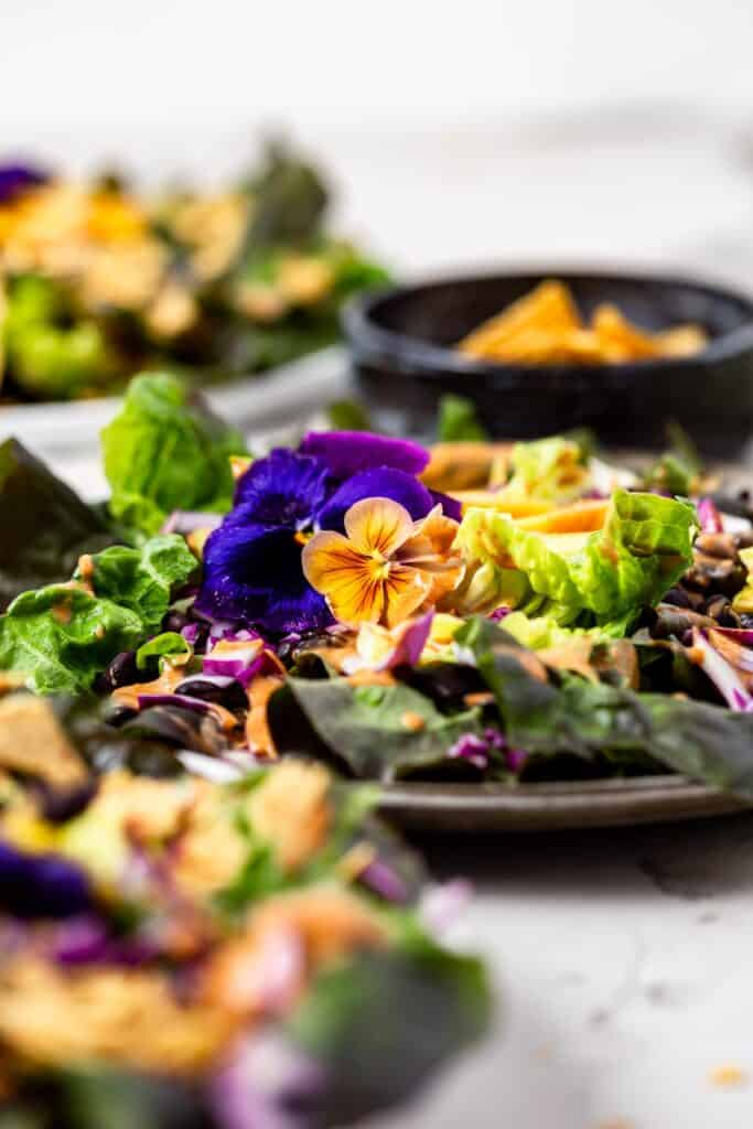 A vegan taco salad topped with purple and yellow-orange flowers