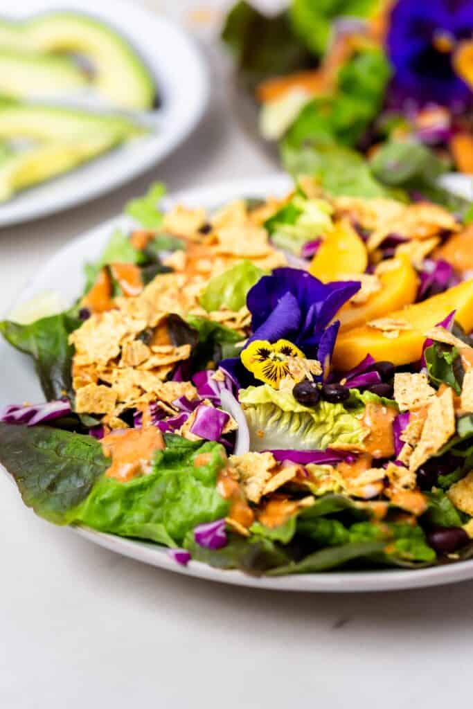 A mango taco salad with purple and yellow pansies on top