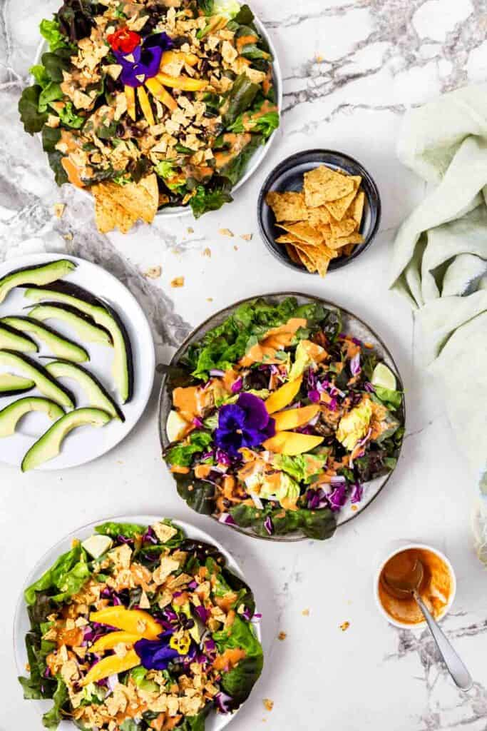 three salads topped with mango beans and edible flowers with a plate of sliced avocado