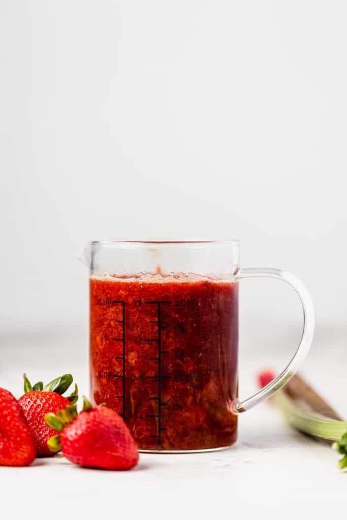 a pitcher of strawberry rhubarb compote surrounded by strawberries and rhubarb