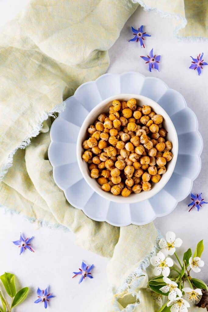 Crispy chickpeas in a bowl surrounded by periwinkle flowers and a green linen