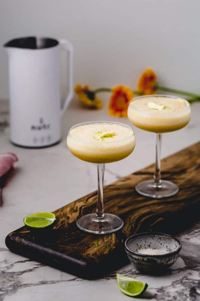 Two Piña Coladas on a wood board with the Nutr Machine in the background.
