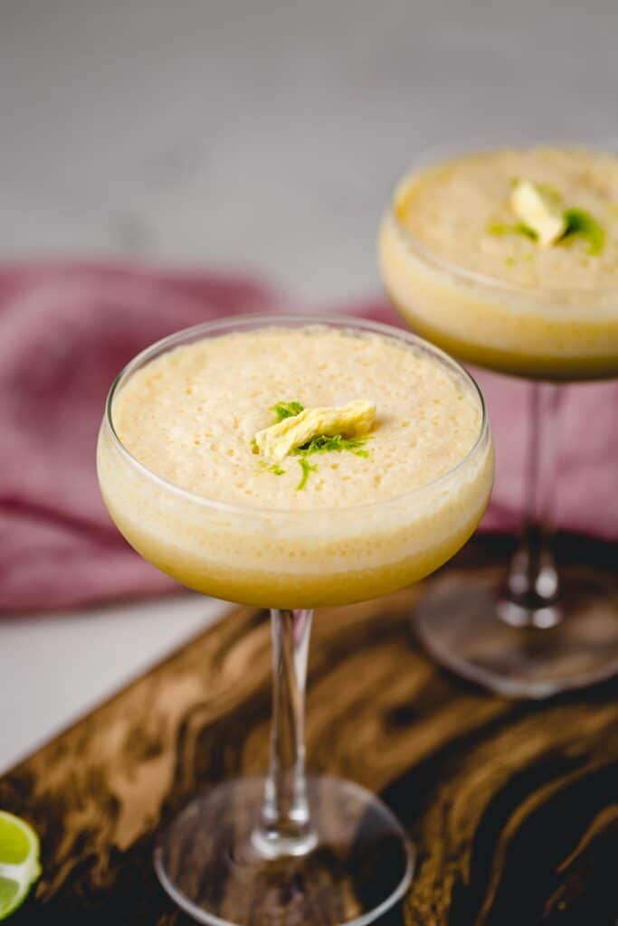 A closeup view of a Piña Colada topped with lime zest and freeze dried pineapple slice.