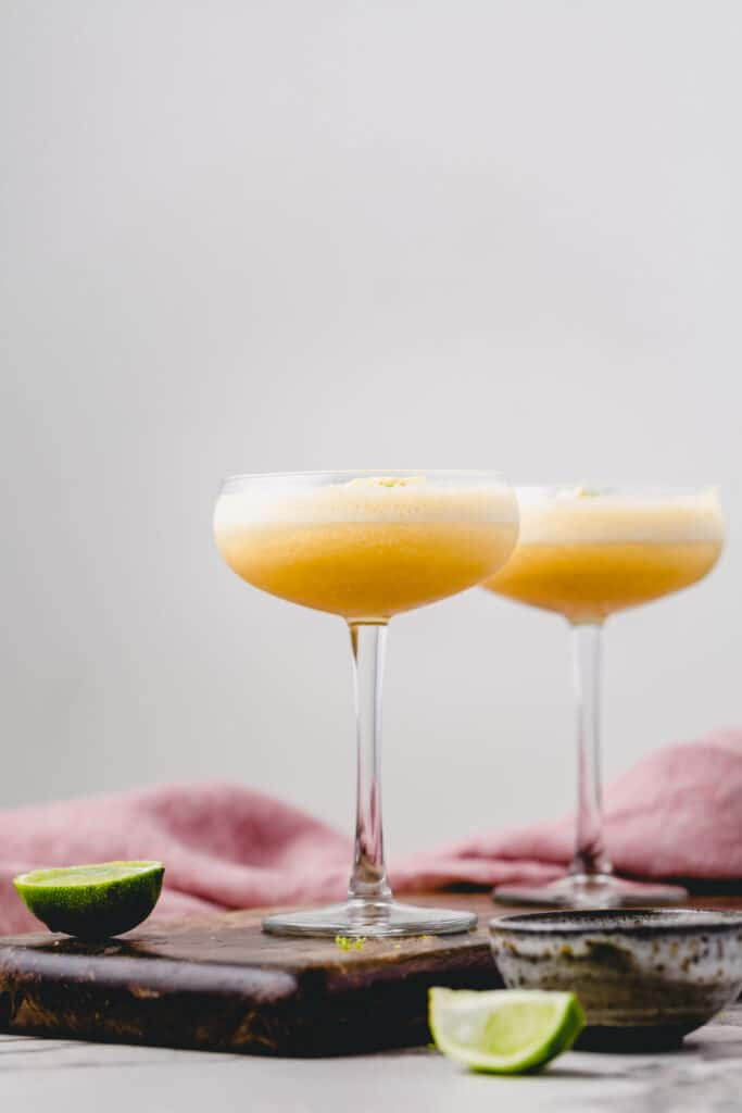 Two Piña Colada cocktails surrounded by lime wedges.