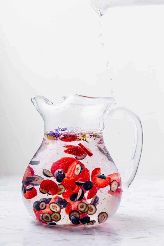 Berries and herbs flavoring water in a large pitcher