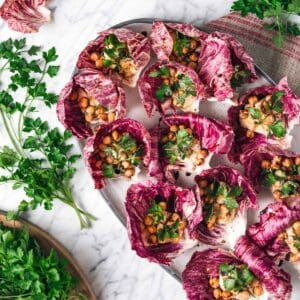 parsley surrounding a platter of radicchio leaves filled with hummus